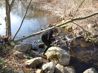 A volunteer monitor checks the water temperature on the Millers River in Cumberland, RI
