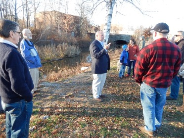 Gene Bernat speaking to group on the bank of the canal