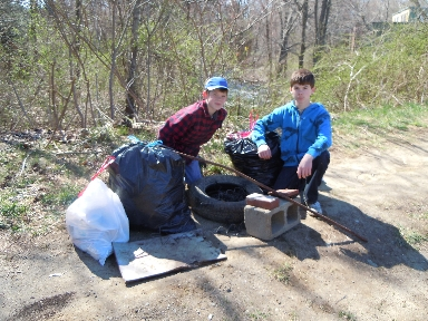Two young volunteers with a pile of trash